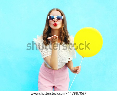 Pretty young woman in sunglasses with air balloon sends an air kiss over colorful blue background #447987067