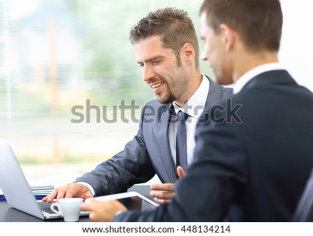 Two confident business people in formalwear discussing something  with laptop and tablet while sitting at the office #448134214
