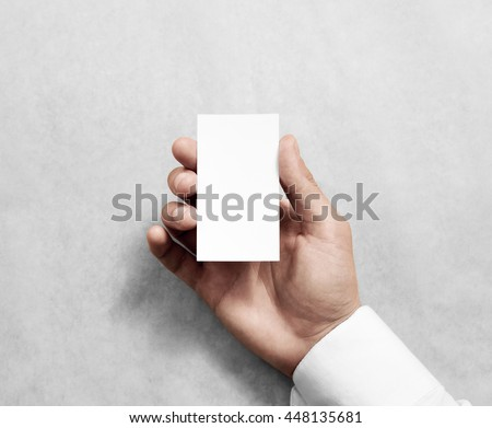 Hand holding blank vertical white business name card mock up.