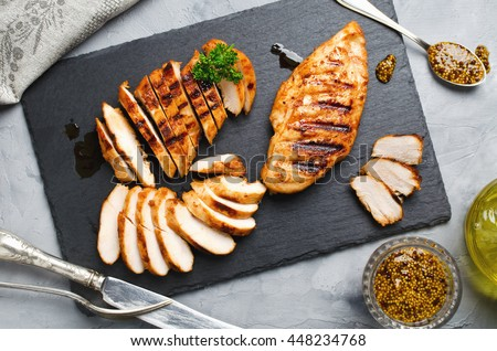 Grilled chicken fillets on slate plate. Gray concrete background Royalty-Free Stock Photo #448234768