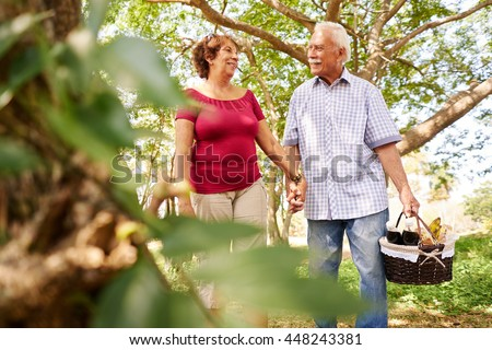 Old couple, elderly man and woman in park. Active retired seniors holding hands and walking in park with a picnic basket