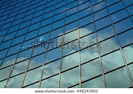 airplane reflect on a glass curtain wall with blue cloudy sky #448245802