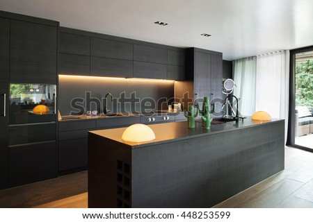 Modern kitchen with black furniture and wooden floor Royalty-Free Stock Photo #448253599