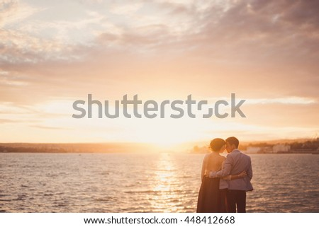 Romantic and stylish caucasian couple hugging at sunrise. Love, relationships, romance, happiness concept. #448412668