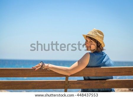Pretty young woman in a straw hat sitting alone on a bench in front of the sea. #448437553