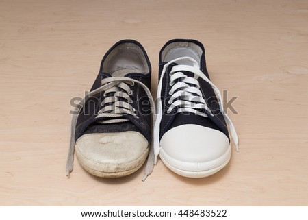 One old dirty shabby sneaker and one new clean unworn sneaker are forming together the whole shoe pair. Sports trendy canvas shoes. Comparison of old and new item. Close-up shot #448483522