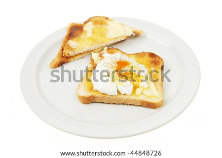 Poached egg on toast on a plate isolated against white #44848726