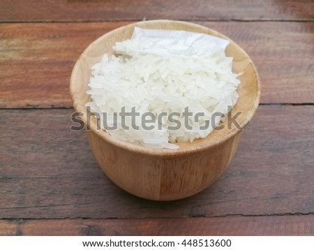 Selective focus on white sticky rice in wooden bowl on the wooden table. #448513600