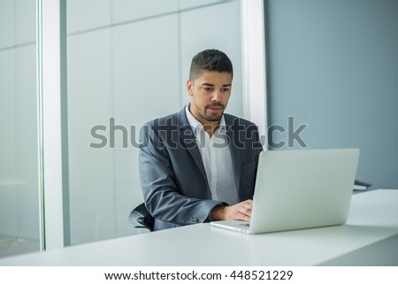 Young businessman lawyer with laptop, alone in big bright conference room. #448521229