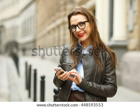 Businesswoman walking down the street while talking on smart phone. Happy smiling caucasian business woman busy #448593553