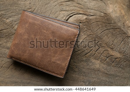 Leather wallet on wood texture Royalty-Free Stock Photo #448641649