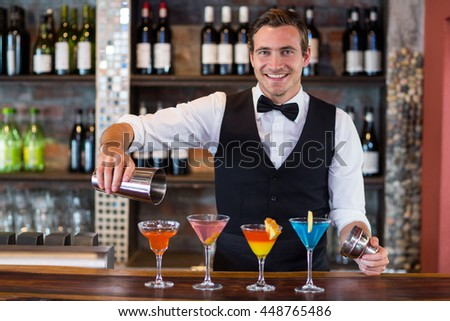 Portrait of bartender pouring a orange martini drink in the glass at bar #448765486
