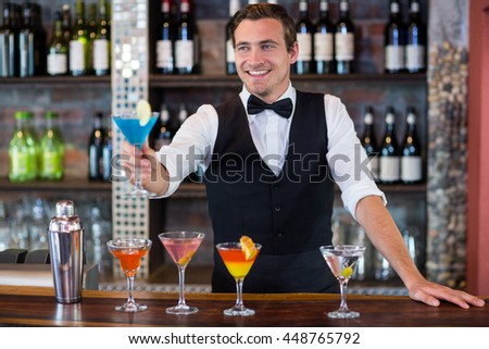 Happy bartender serving a blue martini in bar #448765792