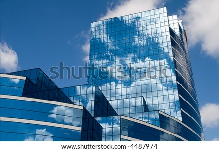 Clouds and blue sky reflect in the windows of a contemporary office building #4487974