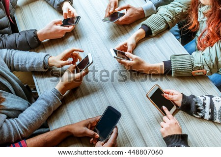 people using smart phones with touchscreen technology - cropped image top view of hands and phones of a group of friends sitting at a table
