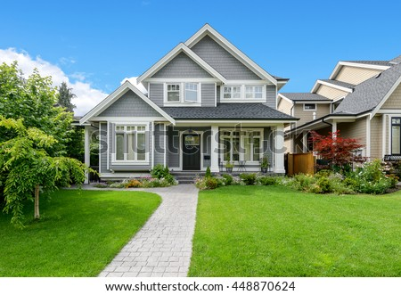 Luxury house with beautiful landscaping on a sunny day. Home exterior. #448870624