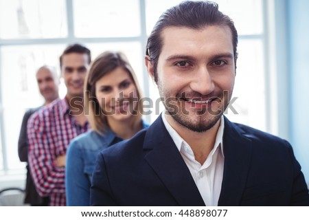 Portrait of smiling businessman with colleagues standing in row at creative office #448898077