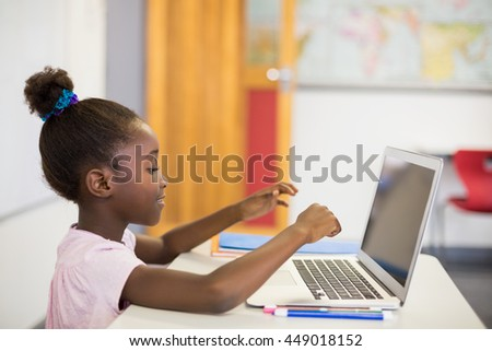 Schoolgirl using laptop in classroom at school #449018152