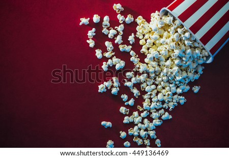 Spilled popcorn on a red background, cinema, movies and entertainment concept Royalty-Free Stock Photo #449136469