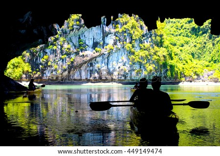 The silhouettes of people kayaking inside of a cave in Lan Ha Bay, close to Halong Bay, Vietnam Royalty-Free Stock Photo #449149474