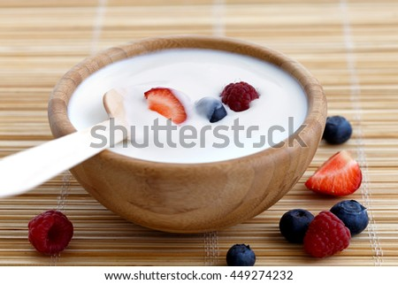 Wooden bowl of white yogurt with wooden spoon inside on bamboo matt. Next to berries. #449274232