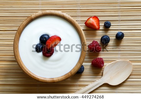 Wooden bowl of white yogurt on bamboo matt from above with wooden spoon. Next to berries. #449274268