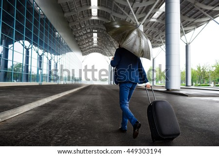 Picture of  young  businessman holding  suitcase and umbrella at rainy airport #449303194
