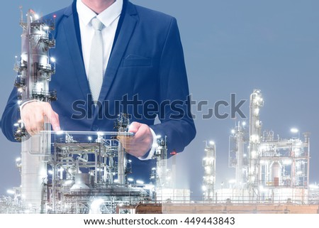 Double exposure of businessman hand hold tablet, oil refinery industry plant, Petroleum energy concept #449443843