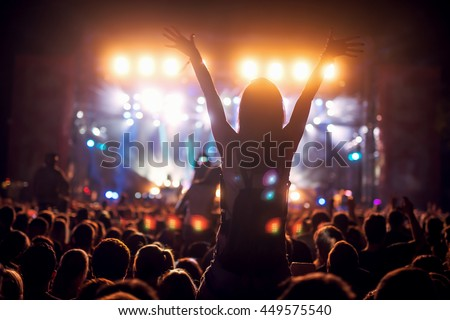 Girl on shoulders in the crowd at a music festival. #449575540