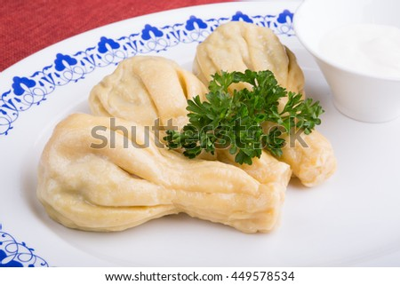 Traditional caucasian dumplings served with sour cream #449578534