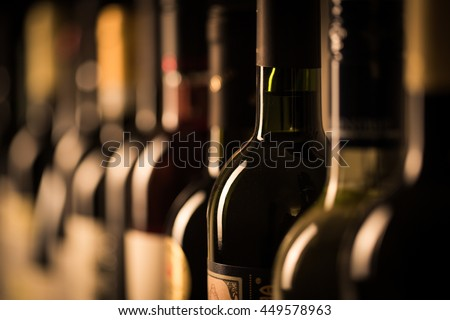 Row of vintage wine bottles in a wine cellar (shallow DOF; color toned image) Royalty-Free Stock Photo #449578963