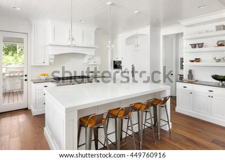 White Kitchen Interior with Island, Sink, Cabinets, and Hardwood Floors and Built In Shelving in New Luxury Home with Lights Off #449760916