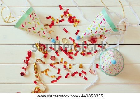 Party hat next to colorful confetti on wooden table. Top view