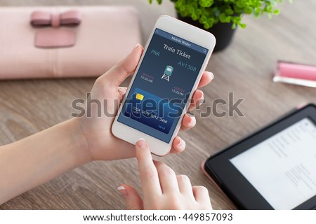 female hands holding white phone with online train ticket and e-rider #449857093