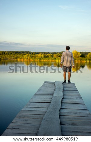 Alone man standing on the edge of a pier on the lake #449980519