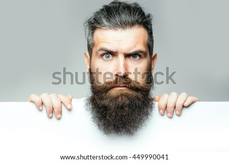 handsome bearded man with long lush beard and moustache on surprised face with white paper sheet in studio on grey background, copy space Royalty-Free Stock Photo #449990041