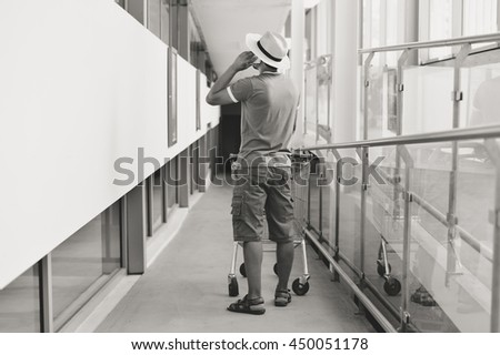 Back view of male person walking talking on mobile smart phone holding shopping cart on store background. #450051178