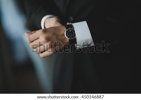 Man in a suit adjusts his black watch on the wirst Royalty-Free Stock Photo #450146887
