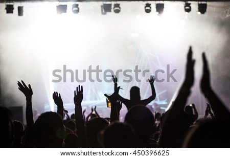 Crowd at concert - Cheering crowd in front of bright colorful stage lights #450396625