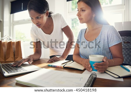 Two young female businesswomen doing research together browsing the internet on a laptop computer in a concept of entrepreneurship and startup small business #450418198