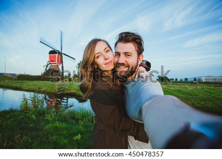 Happy young couple in love takes selfie portrait in front of the mill near Amsterdam while travel in Netherlands, Europe.