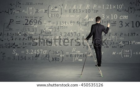 A businessman in elegant suit standing on a small ladder and writing numbers, calculating on grey wall background #450535126
