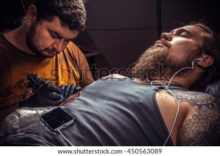 Tattooist makes tattoo in tatoo salon. #450563089