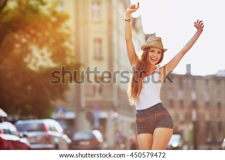 Happiness concept - happy woman having fun on city street during summer #450579472