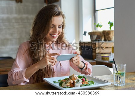 Female blogger photographing lunch in restaurant with her phone #450580369