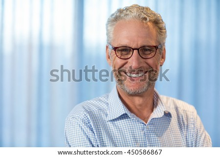Portrait of man smiling in office #450586867
