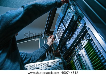 Operator Master repairs computer servers in a server room, close-up Royalty-Free Stock Photo #450746512