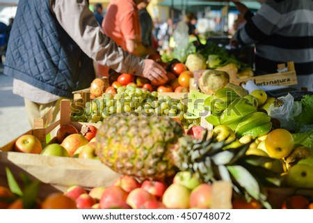 Sale, consumerism concept and pineapple with fruits on grocery market stall background. Closeup on person hand shopping for fresh food #450748072