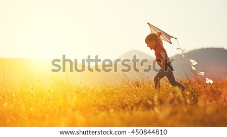 happy child girl with a kite running on meadow in summer in nature #450844810
