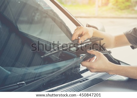 Man is changing windscreen wipers on a car ,picture vintage style Royalty-Free Stock Photo #450847201